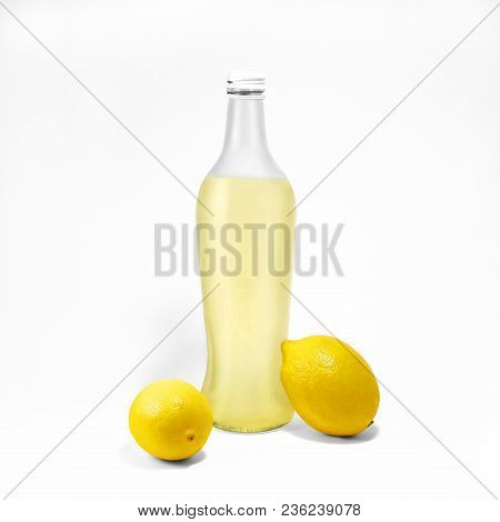 Transparent Glass Bottle With Lemonade And Two Whole Lemons Near Are Standing On White Background Ph