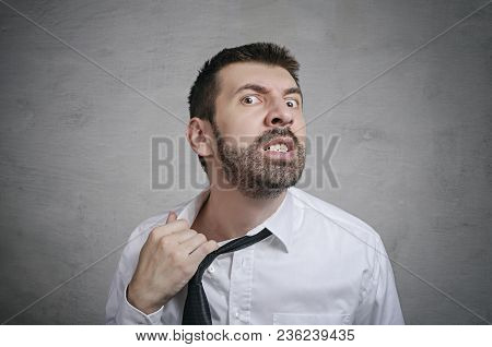 Portrait Of Rage Businessman With Beard Taking Off His Tie. Concept Of Anger.
