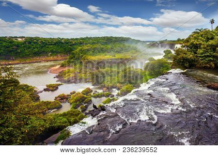 Travel to Argentina. Huge complex of waterfalls Iguazu on the border of three countries. Picturesque basaltic ledges form the famous waterfalls. The concept of exotic and active tourism