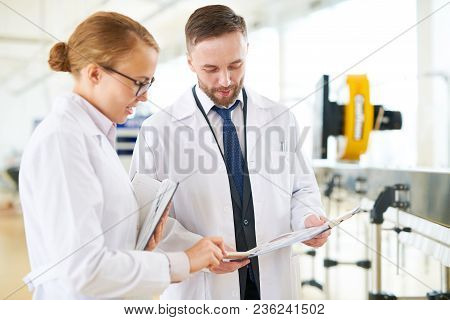 Bearded Technologist And His Pretty Colleague Wearing White Coats Standing At Modern Equipment Of Da