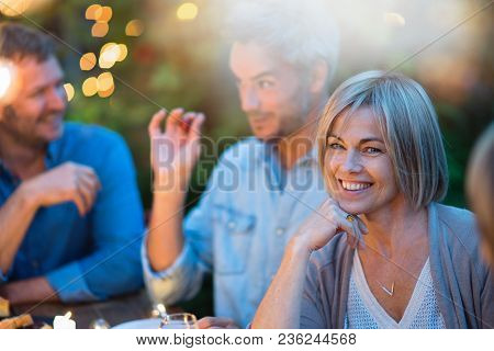 One Summer Evening, Friends Gathered Around A Table In The Garden Lit By Light Garlands. Focus On A