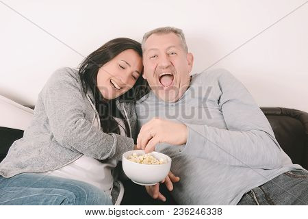 Latin Middle-aged Couple Laughing, Eating Popcorn And Watching A Movie Together. Indoors