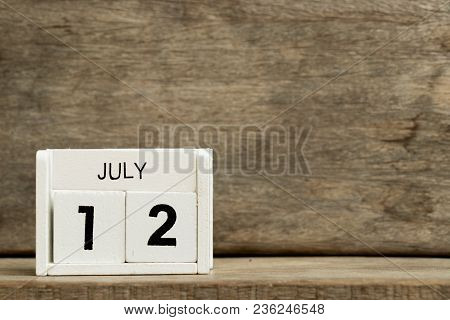 White Block Calendar Present Date 12 And Month July On Wood Background