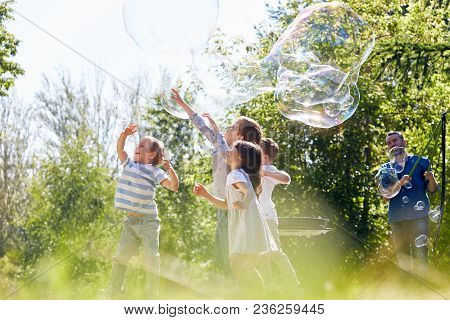 Profile View Of Little Friends Having Fun While Participating In Soap Bubble Show At Green Public Pa