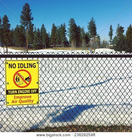 Yellow Sign On Wire Fence With Snowy Ground And Grass In Park. Playground And Tall Pine Trees Under