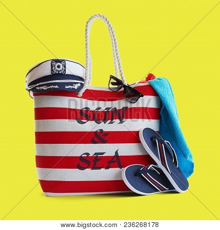 Red Stripe Beach Bag And Other Accessories On Yellow Background