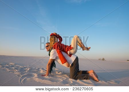 Joyful Crazy Couple Of Travelers Fools Around And Has Fun In Desert On A Sunny Evening. Active Peopl