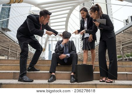 Stress Sad Businessman  Sit On Stair Of Modern City While Other Business Guys Laugh At Him. Head Dow