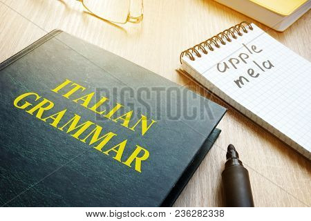 Learn Italian Grammar. Book And Notebook On A Table.