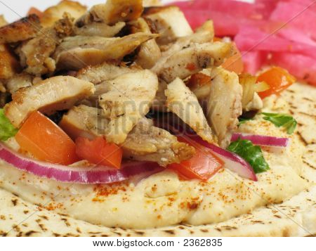 Shawarma style chicken tarna on a pita with hummus fresh vegetables and a side of turnips pickled in beet roots. poster