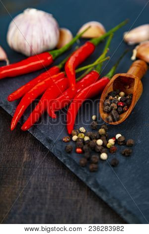 Red Chili Pepper, Garlic And Hot Peppercorns On A Dark Background. Various Spices.