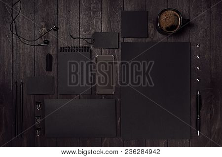 Black Blank Stationery Set With Phone, Earphone, Coffee On Dark Wood Background. Mock Up For Brandin