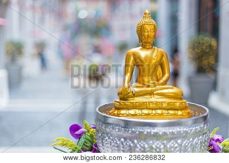 Small Golden Yellow Buddha Statue Setting On A Table At A Local Public Place For People To Prey Resp