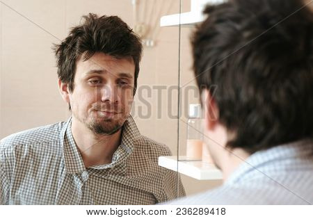 Tired Man Who Has Just Woken Up Looks At His Reflection In The Mirror And Sees His Scruffy Appearanc