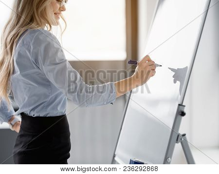 Inspired Businesswoman Noting Her Creative Idea On Board By Marker