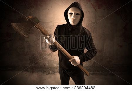 Armed rude assassin in an empty bloody room concept with gun ax chainsaw mallet wrench