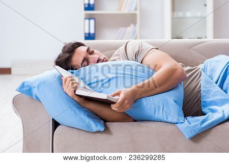 Young student man preparing for college exams in bed with book