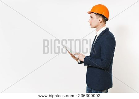 Young Handsome Businessman In Dark Suit, Protective Hardhat Using Tablet Pc Computer And Looking Asi