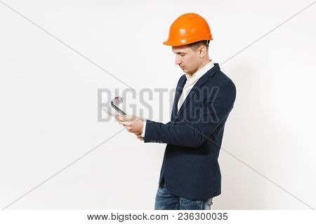 Young Handsome Businessman In Dark Suit, Protective Construction Helmet Looking On Clipboard With Pa