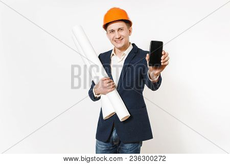 Young Dissatisfied Businessman In Dark Suit, Protective Hardhat Holding Blueprints Plans And Mobile