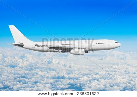 White Passenger Wide-body Aircraft Flies Travel, Trip At The Flight Level Cumulus Clouds, Above Agai