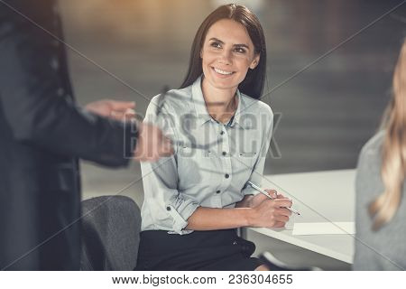 Portrait Of Beaming Young Female Employer Talking With Colleague While Sitting At Table. Glad Girl D
