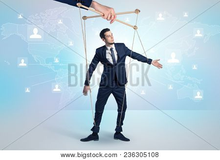 Little businessman controlled from above like a puppet concept