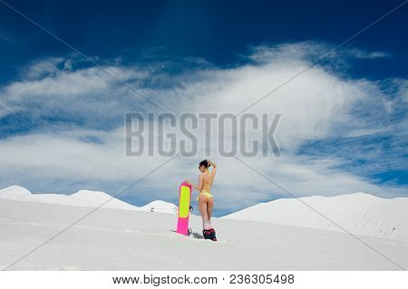 Back View Of A Hot Snowboarder Woman Dressed In A Swimsuit Standing On A Mountain Peak Holding A Pin