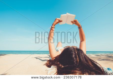 Leisure In Summer - Young Woman Lying On A Tropical Beach, Relax With Book. Blue Sea In The Backgrou