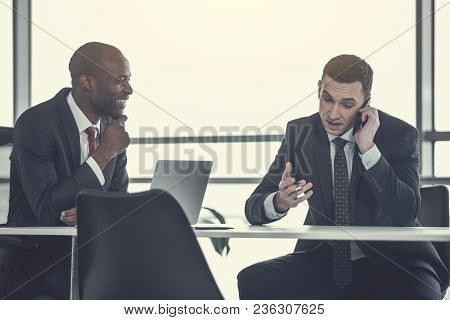 Outgoing Businessman Looking At Dissatisfied Partner. He Talking By Mobile While Gesticulating Hands