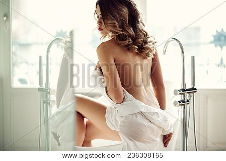 Beautiful Sexy Lady In Elegant White Shirt In A Bathroom. Fashion Portrait Of Model On A Bath Indoor