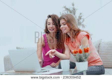two young women discuss the video with laptop sitting at a coffee table