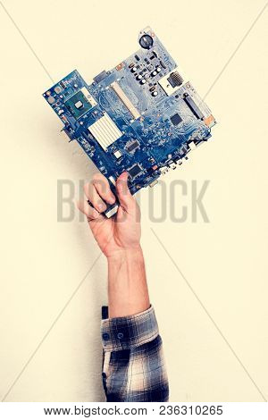 Hand holding motherboard circuit hardware part