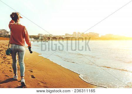 Unrecognizable Hiker Girl In Jeans Walks Along The Seashore With Binoculars, Rear View. Scout Wander