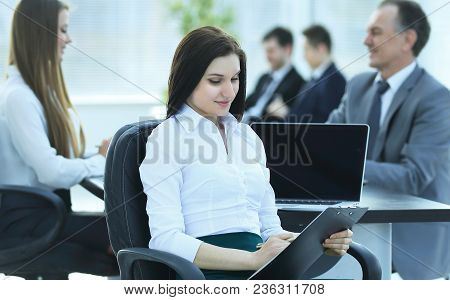 Young Business Business Woman Reading Document, Sitting In The Office .photo With Place For Text