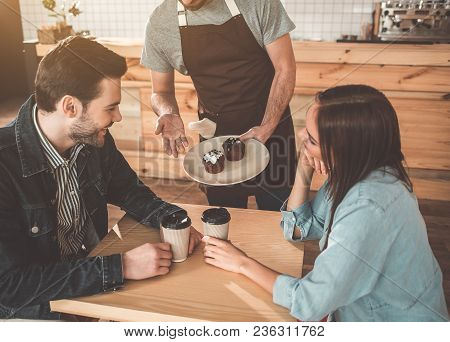 Your Order, Sir. Polite Waiter Is Serving Cakes And Coffee To Clients In Cafe. Couple Is Sitting At
