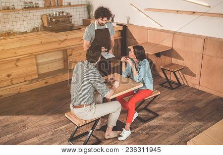 Serious Young Waiter Is Serving Customers With Concentration. He Is Standing Near Couple And Making