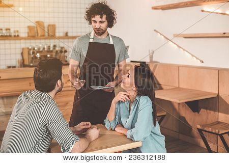 Cheerful Couple Ordering Food And Drink In Cafeteria. They Are Looking At Waiter With Trust And Smil