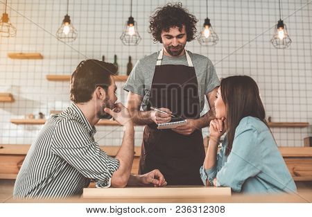 Great Service. Portrait Of Joyful Young Waiter Receiving An Order From Clients. He Is Writing Into N