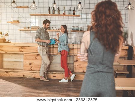 Charming Girl Is Flirting With Man And Smiling. She Is Touching Gift Present In Male Hands With Curi