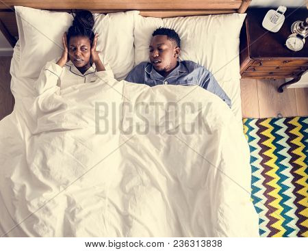 African American couple on bed, man snoring and disrupting woman sleep
