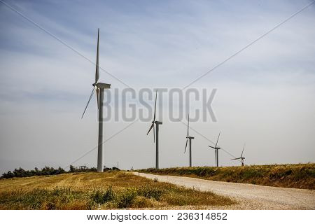 A Row Of Wind Generators On A Field With A Rural Road