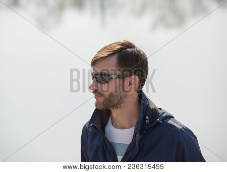 Portrait Of A Bearded Man In Sunglasses On A Light Background. Age Of Forty Years.
