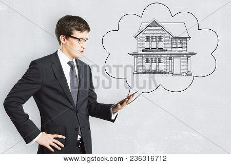 Young European Businessman With Abstract House Sketch In Thought Cloud Drawn On Concrete Background.