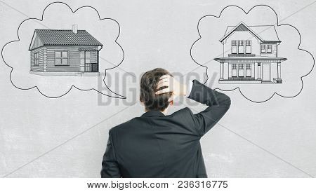 Back View Of Pensive Young European Businessman With Abstract House Sketch In Thought Cloud Drawn On