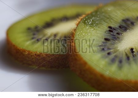 Fruit In Macro. Side View Fresh Fruit. Kiwi Fruit On White Plate. Kiwi Collection. Kiwi Peel In Macr