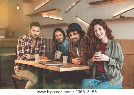 Enjoying Time With Best Friends. Portrait Of Happy Young Men And Women Drinking Coffee In Cafe. They