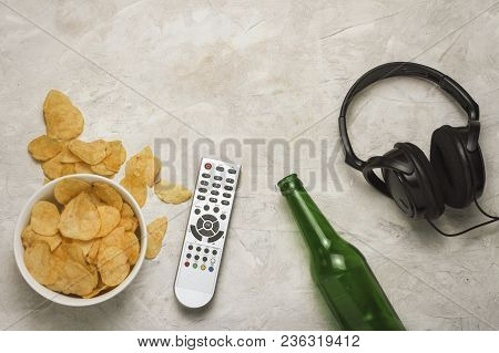 Tv Remote, A Bowl Of Chips And A Bottle Of Beer On A Light Background Stone. Flat Lay, Top View.