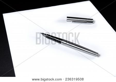 On A White Sheet Of Paper Is An Ink Pen With A Cap.