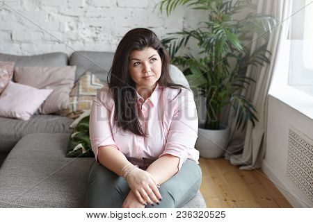 Portrait Of Attractive Young Overweight Dark Haired Woman Daydreaming Indoors, Planning Her Day, Sit